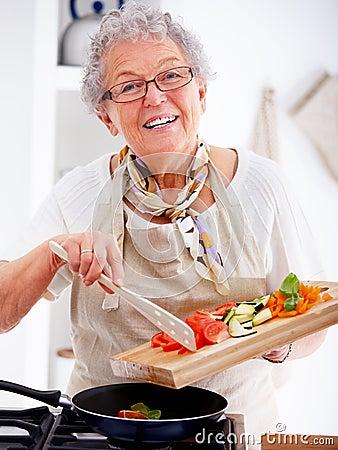Stock afbeeldingen friendly older woman happily cooking a meal beeld 7299304 for Beeldkoken