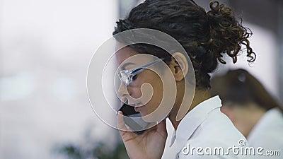 Vrij biracial vrouw die op cellphone spreken, die cliënt overreden om een aankoop te maken stock videobeelden