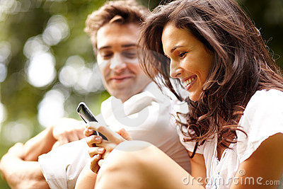 Vrij het jonge vrouw gebruiken mobiel met haar vriend