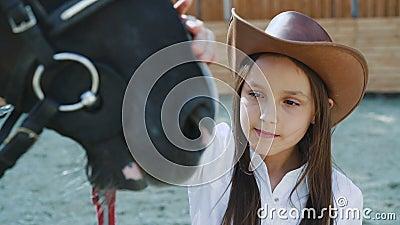 Vrij vrouwelijke tiener die vriendschappelijk zwart paard op een gebied ceressing 4K stock video