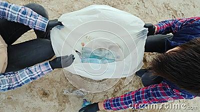 Vrijwilligers plaatsen plastic afval in een zak Het strand schoonmaken, zorgen voor het milieu Bovenaanzicht stock videobeelden