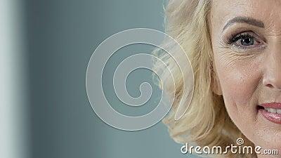 Vrolijk hoger blonde die in camera, plastische chirurgiekliniek, close-up glimlachen stock footage