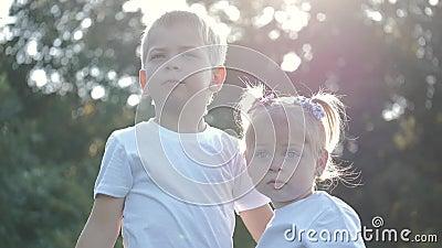 Vrolijke broer en zus die in de openlucht op het platteland spelen Zomerentertainment voor kinderen Gezonde levensstijl stock videobeelden