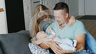 Vrolijke familie met een baby thuis Moeder, vader en zoon twee maanden Concept - echtelijk geluk, het comfort van thuis, een stock footage
