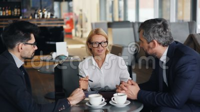 Vrolijke het bedrijfsdame onderhandelen overeenkomst met mannelijke partners die in koffie samenkomen stock footage