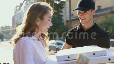 Vrolijke jonge bezorger die een pizzadoos houden terwijl geïsoleerd op wit Het Voedsel van koeriersdelivering box with aan Cliënt stock footage