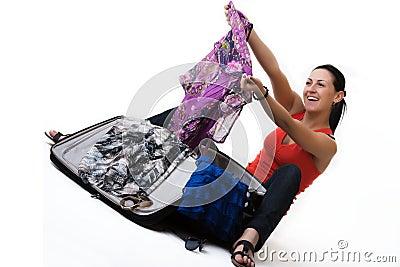 Gelukkige reisvrouw die haar koffer uitpakken