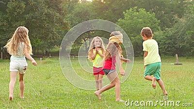 Vrolijke kinderen die markering met het slaan van het gras op een de zomerdag spelen Langzame Motie stock footage