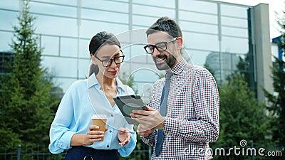 Vrolijke mensen zakenpartners die buiten lachen met tabletcomputer stock videobeelden
