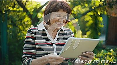 Vrolijke Oude die Vrouw door Skype wordt verbonden stock footage