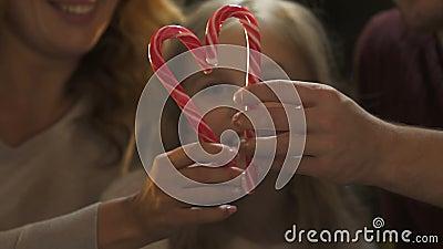 Vrolijke ouders die hart van suikergoedriet vormen, fonkelende Kerstmisdecoratie stock videobeelden