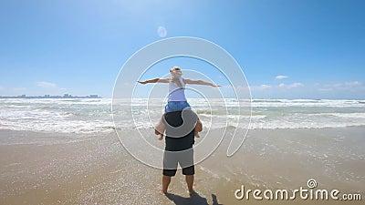 Vrolijke vader en dochter spelen op het strand tijdens een zeesstorm Begrip vriendschappelijk gezin, reizen, levensstijl stock video