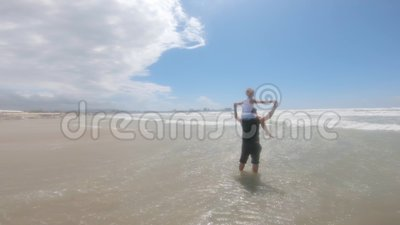 Vrolijke vader en dochter spelen op het strand tijdens een zeesstorm Begrip vriendschappelijk gezin, reizen, levensstijl stock videobeelden