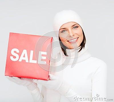 Vrouw in de winterkleren met rood verkoopteken