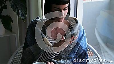 Vrouw in deken wordt verpakt die mobiele telefoon die 4k met behulp van stock videobeelden