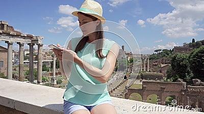Vrouw dichtbij Roman mobiel forumgebruik De vrouwelijke toerist zoekt richting via online app met stadskaart stock videobeelden
