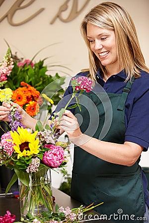 Vrouw die in bloemist werkt