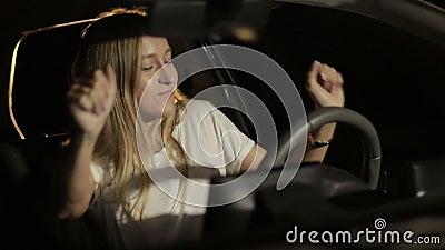 Vrouw die dansbewegingen maken bij nacht in auto stock videobeelden