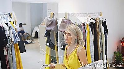 Vrouw die de gele kleding in de Boutique passen Modieus en modieus meisje die voor de spiegel blijven Jongelui en stock video