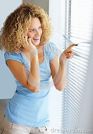Vrouw die door venster kijkt terwijl het spreken