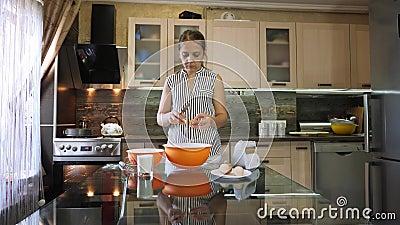 Vrouw die een ei in een kom barsten Het scheiden van dooier van proteïne Het voorbereiden van een deeg stock videobeelden