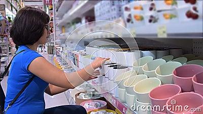 Vrouw die een mok in de opslag kopen stock footage