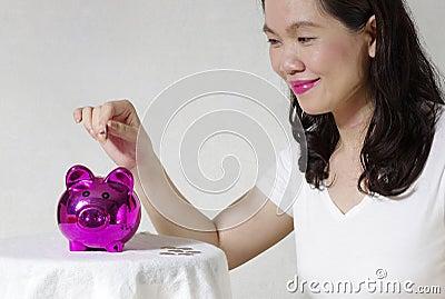 Vrouw die een muntstuk zetten in spaarpot