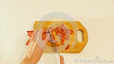 Vrouw die een rode peper snijdt op de keukenkamer stock video