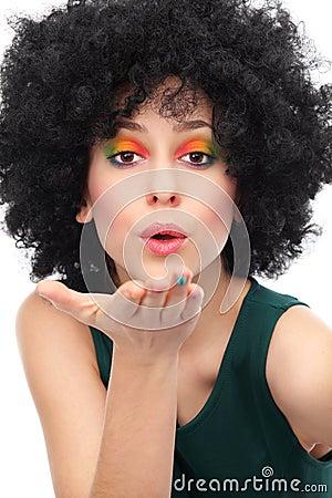 Vrouw die met afro een kus blazen