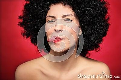 Vrouw die met afro haar tong uit plakken