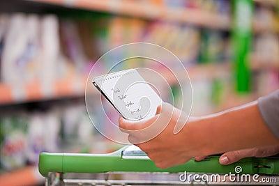 Vrouw die met Controlelijst en Karretje winkelt