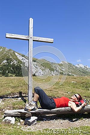 Vrouw die onder houten kruis rusten