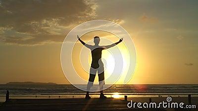 Vrouw die ontspanningsoefeningen doen bij zonsopgang stock videobeelden