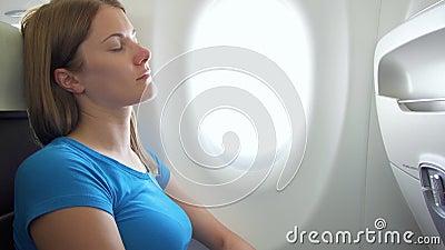 Vrouw die in vliegtuig in dag vliegen Vermoeid door straalvertragings vrouwelijke slaap dichtbij venster tijdens onstuimigheid stock videobeelden
