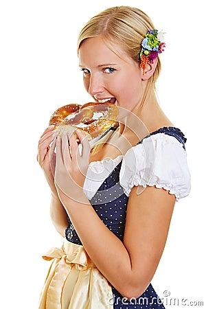 Vrouw in dirndl het bijten in een pretzel