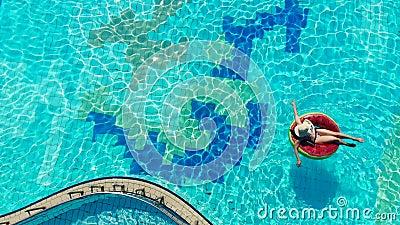 Vrouw drijft op een rubberen ring in een groot zwembad stock videobeelden