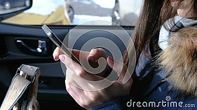 Vrouw in een auto met een mobiele telefoon De handen die van de close-upvrouw ` s in telefoon babbelen stock footage