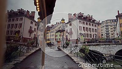 Vrouw in een felgele jas met een paraplu loopt over de brug door een kanaal in het regenachtige weer Annecy, Frankrijk stock videobeelden