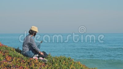 Vrouw in het riet die een laptop gaat gebruiken op een mooie kustlijn stock videobeelden