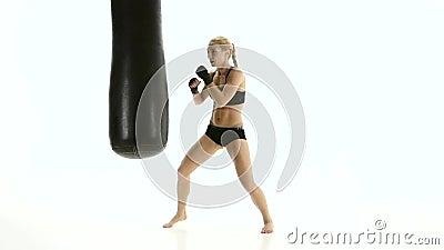 Vrouw kickboxer met hartstocht die met een ponsenzak opwarmen stock videobeelden