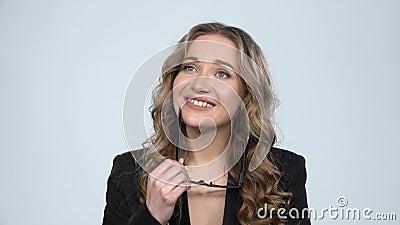 Vrouw kijkt met een glimlach naar de camera, neemt haar bril af en droom ergens over, trage beweging stock videobeelden