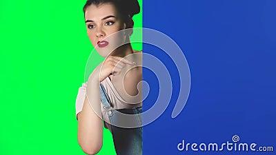 Vrouw kijkt uit van achter een blauw blanco bordje en roept zichzelf op om scharnierend te zijn, trage beweging stock footage
