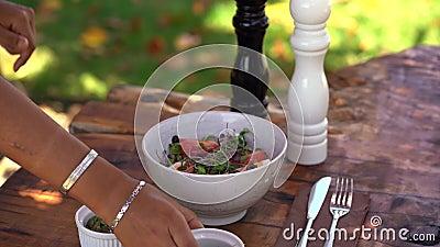 Vrouw kruipt een verse salade met sla, tomaat, eieren en olijven Pompoenzaad, boonkiemen en zout en peper stock videobeelden