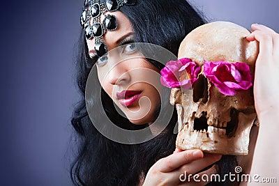 Vrouw met een bleke gezicht en een schedel.