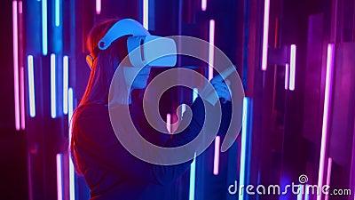 Vrouw met een snelle helling van de VR-headset van zijkant naar zijkant terwijl hij speelt in een donkere ruimte verlicht neonlic stock video