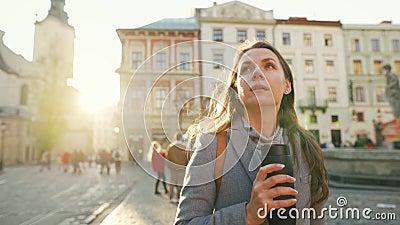 Vrouw met een thermobeker in de hand die door de straat loopt en bewondert de architectuur van de oude stad bij zonsondergang op  stock videobeelden