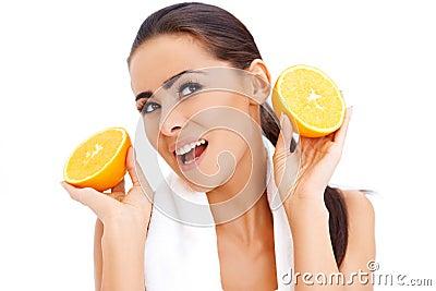 Vrouw met verse sinaasappel halfs in haar handen