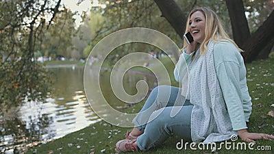 Vrouw plus grootte zit op de achtergrond van Lake Bank Park stock footage