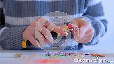 Vrouw schilder scherpend rood potlood met scherp mes, handen dichtmaken stock video