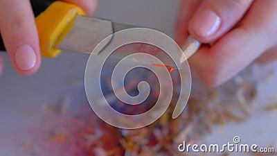 Vrouw schilderaar die oranje potlood scherpt met scherp mes, handen dichtsbijt stock videobeelden